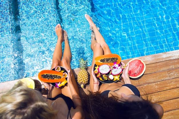 Due belle ragazze bionde e castane si divertono e impazziscono alla festa dei frutti tropicali, bikini nero sexy, tanto dolce cibo vegano, vacanze esotiche, posa vicino alla piscina, immagine di moda estiva.
