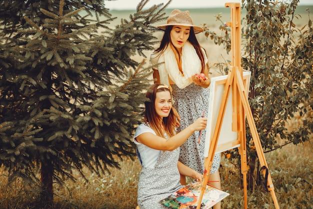 Due belle ragazze che disegnano in un campo