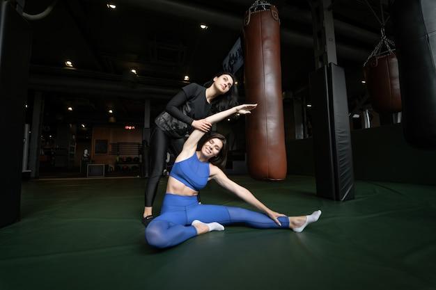 Due belle ragazze che fanno forma fisica in una palestra. allungando i muscoli delle gambe e delle braccia.