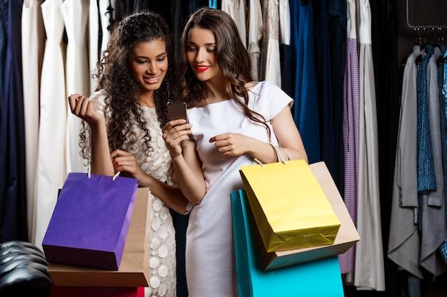 Due belle ragazze che fanno shopping, guardando il telefono nel centro commerciale.