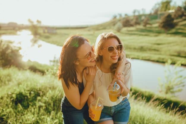Due belle ragazze che si divertono l'estate bevono i cocktail, al tramonto, espressione facciale positiva, all'aperto