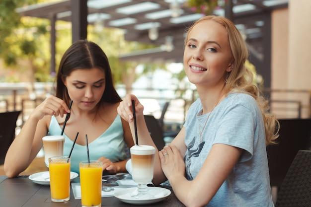 Due belle ragazze che si siedono al tavolo nella caffetteria