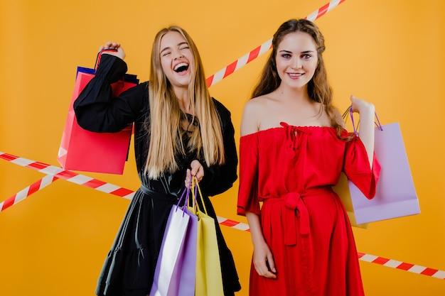 Due belle ragazze con i sacchetti della spesa variopinti e nastro adesivo isolato sopra giallo