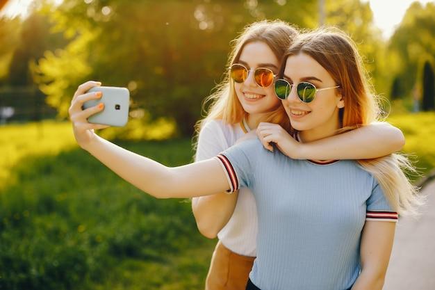 Due belle ragazze giovani belle con capelli biondi lucenti e una gonna e camminare