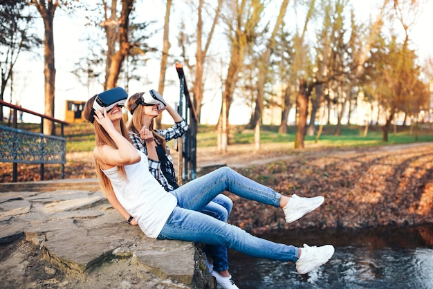 Due belle ragazze godono di occhiali per realtà virtuale all'aperto