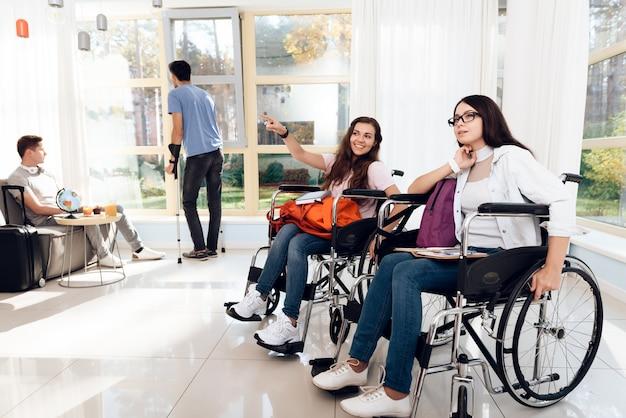 Due belle ragazze in sedia a rotelle nel salotto dell'aeroporto.