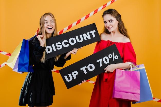 Due belle ragazze sorridenti hanno uno sconto fino a 70 segno con i sacchetti della spesa variopinti e nastro adesivo isolato sopra giallo