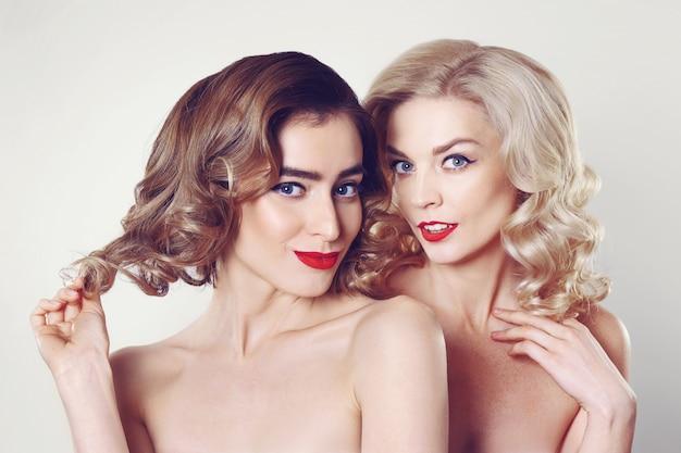 Due belle ragazze spettegolare con trucco e acconciatura professionali