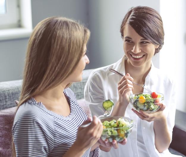 Due belle ragazze stanno mangiando insalata.