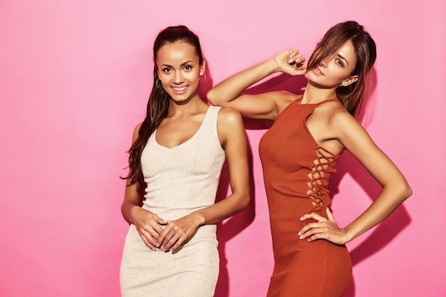 Due bellissime modelle sexy sorridenti indossano un abito in cotone di tendenza con un design alla moda, stile estivo casual per un appuntamento con una passeggiata. donne calde della donna di affari del brunette che propongono sulla parete dentellare