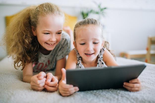 Due bellissime sorelline sdraiate sul letto e guardare lo schermo di un tablet, bambini intelligenti che usano la tecnologia intelligente