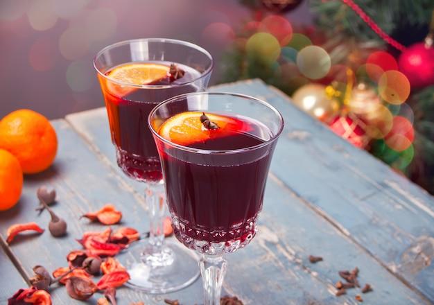 Due bicchiere di vino con natale vin brulè con spezie e frutta su un tavolo in legno rustico.