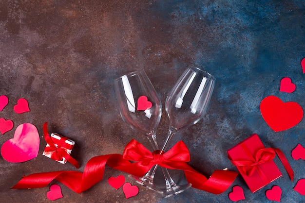 Due bicchiere di vino, cuori e scatola regalo su fondo di pietra. san valentino