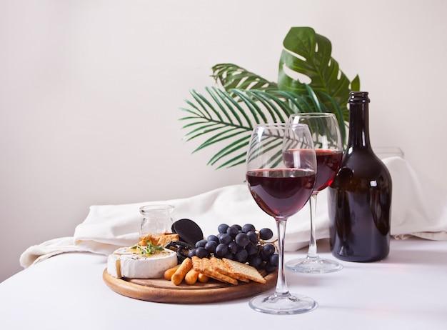 Due bicchiere di vino rosso e piastra con formaggi assortiti, frutta e altri snack per la festa