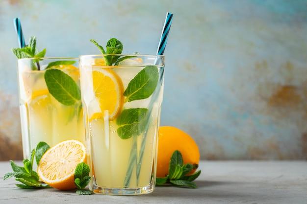 Due bicchieri con cocktail di limonata o mojito con limone e menta, bevanda o bevanda rinfrescante fredda