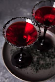 Due bicchieri con cocktail rosso per la festa di halloween sul buio