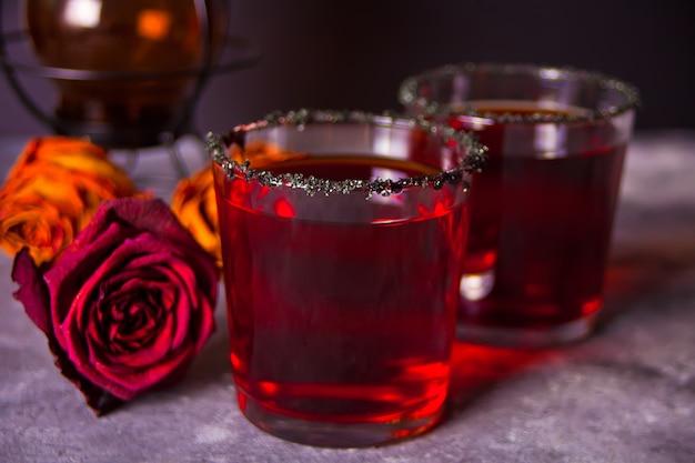 Due bicchieri con cocktail rosso, rose secche per la festa di halloween al buio