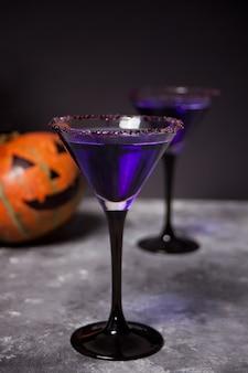 Due bicchieri con cocktail viola, zucca per la festa di halloween al buio