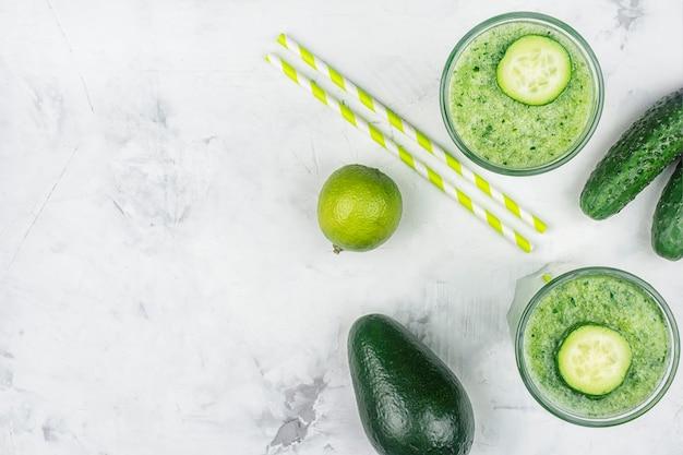 Due bicchieri con frullato di cetriolo, avocado e cannucce. copia spazio. beneficio del concetto di succo di cetriolo.