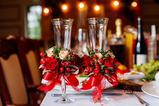 Due bicchieri da sposa vuoti, decorati con verde, rose rosse e nastro, in piedi sul tavolo del banchetto