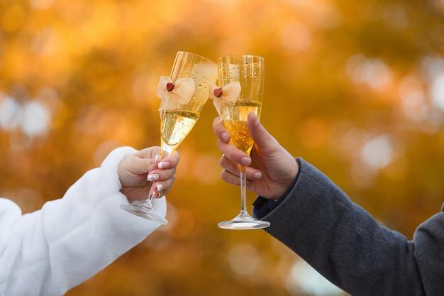 Due bicchieri decorati con uno champagne nelle mani della sposa e dello sposo.