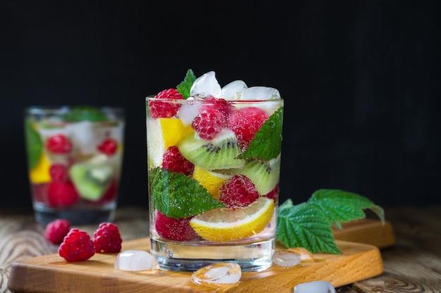 Due bicchieri di acqua minerale fresca, con bacche e frutti (lampone, limone, kiwi, ciliegia) e ghiaccio su sfondo nero