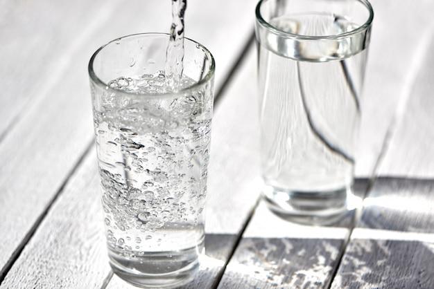 Due bicchieri di acqua su uno sfondo sfocato. versa dell'acqua in un bicchiere.