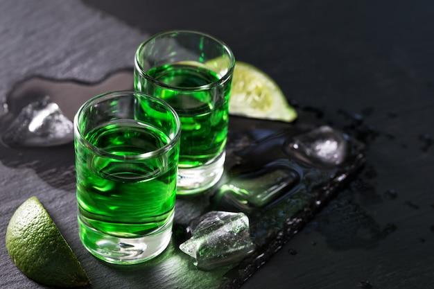 Due bicchieri di assenzio con ghiaccio sciolto e fettine di lime
