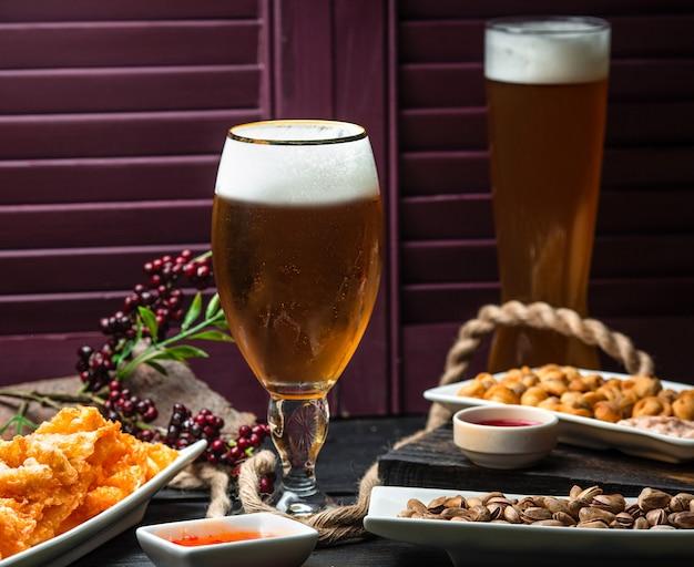 Due bicchieri di birra serviti con pepite, salsa di peperoncino dolce e frutta secca