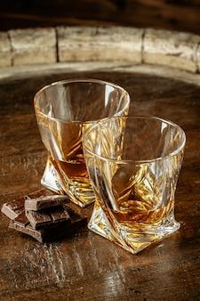 Due bicchieri di bourbon o scotch, o brandy e pezzi di cioccolato fondente