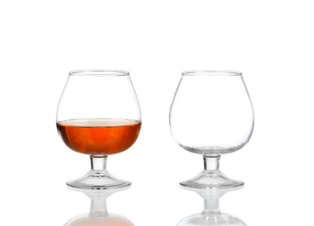Due bicchieri di brandy (vuoti e con alcool) isolati su bianco