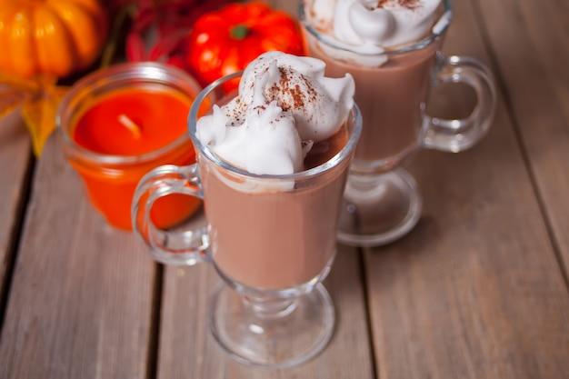 Due bicchieri di cacao caldo cremoso con schiuma con foglie di autunno e zucche sullo sfondo