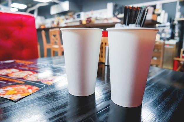 Due bicchieri di carta bianca con caffè sul tavolo del caffè