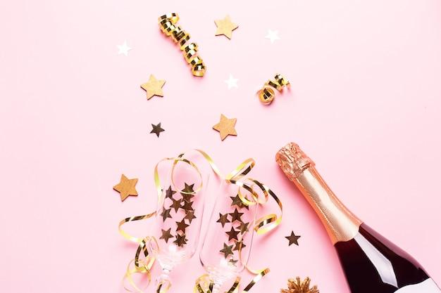 Due bicchieri di champagne con coriandoli e stelle filanti, bottiglia di champagne dorata