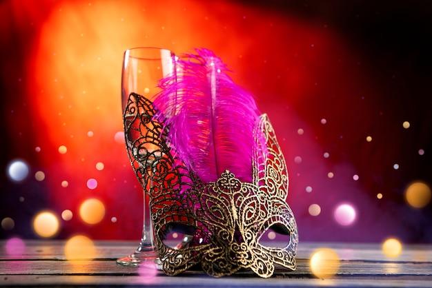 Due bicchieri di champagne con maschera sul tavolo