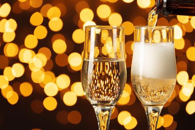 Due bicchieri di champagne contro il bokeh splendente sfondo luci