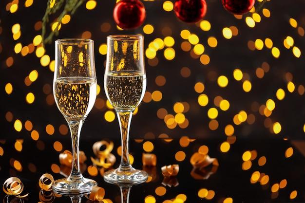 Due bicchieri di champagne e palline di natale su sfondo di luci bokeh splendente