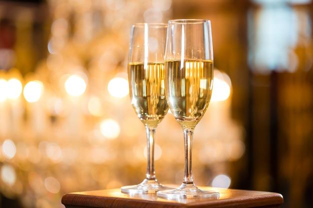 Due bicchieri di champagne in un raffinato ristorante, un grande lampadario è dentro