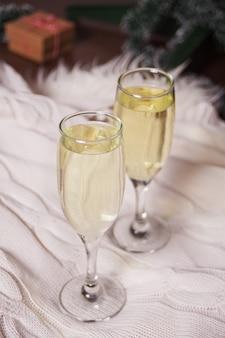 Due bicchieri di champagne su un plaid di pelliccia bianca
