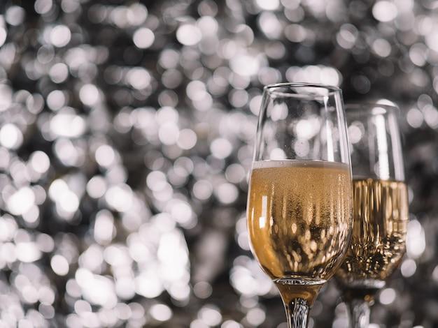 Due bicchieri di champagne su uno sfondo d'argento. copyspace di natale e capodanno