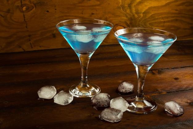Due bicchieri di cocktail blu dentro su fondo di legno scuro