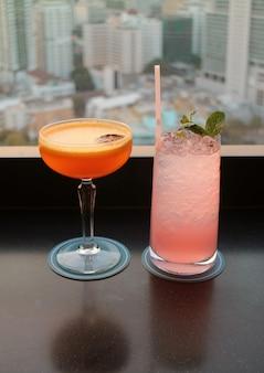 Due bicchieri di cocktail sulla barra sul tetto con sfocata vista aerea urbana in background.