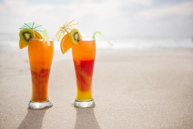 Due bicchieri di cocktail tenuti sulla sabbia