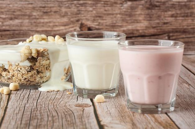 Due bicchieri di fragola sana e yogurt classico con avena sul tavolo di legno. colazione salutare. chiudere con copia spazio. yogurt freschi fatti in casa con cereali, due bicchieri di latticini.