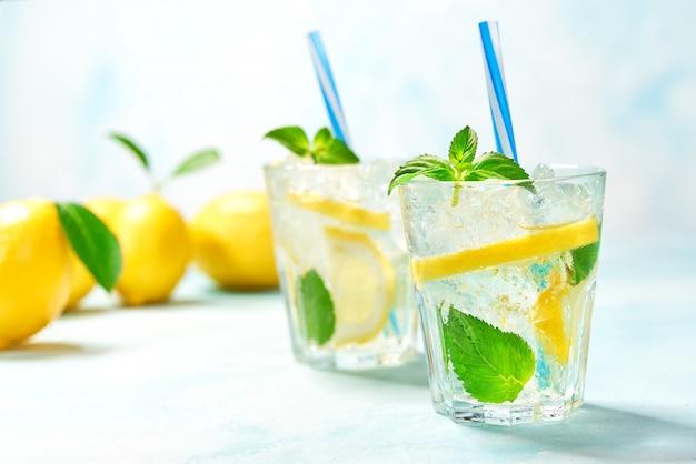 Due bicchieri di limonata con limone fresco su sfondo turchese