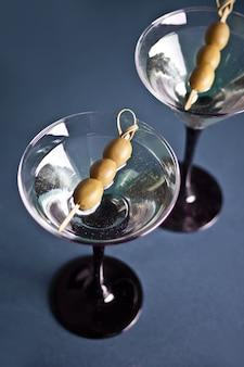 Due bicchieri di martini con olive sul blu.