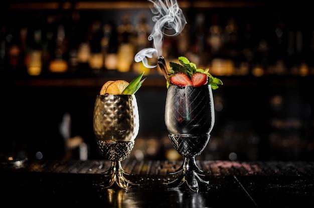 Due bicchieri di metallo di freschi cocktail estivi decorati con frutta sul bancone del bar