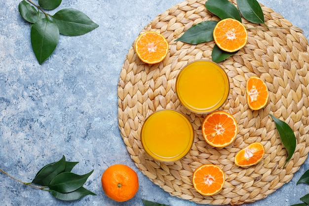 Due bicchieri di succo d'arancia fresco biologico con arance crude, mandarini