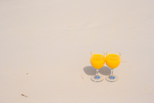 Due bicchieri di succo d'arancia sulla spiaggia bianca tropicale
