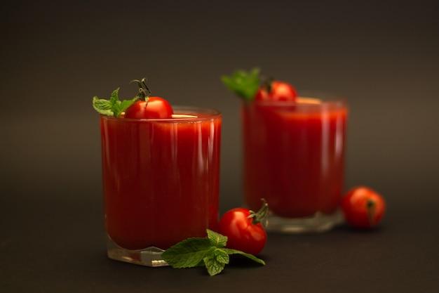 Due bicchieri di succo di pomodoro con pomodorini e menta con uno sfondo nero